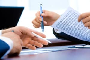 surety underwriting - tow people looking at documents contracts