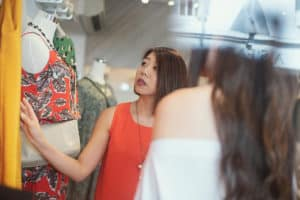retail business - woman wearing red dress looking at clothes in a retail store