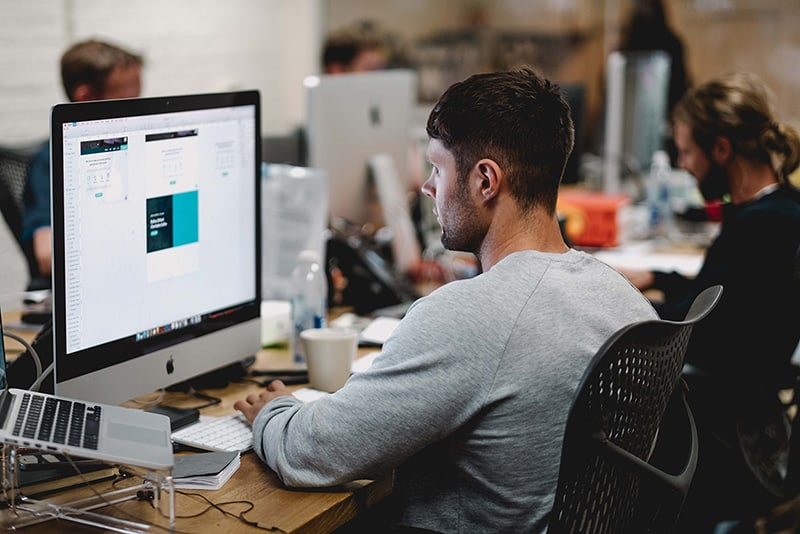 man in gray sweatshirt sitting on chair in front of iMac - recruitment hiring from within