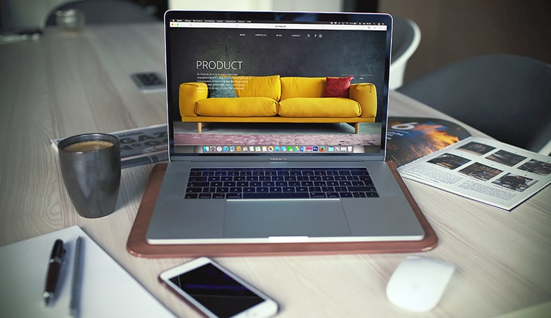 ecommerce online store shown on open MacBook Pro beside a gray mug
