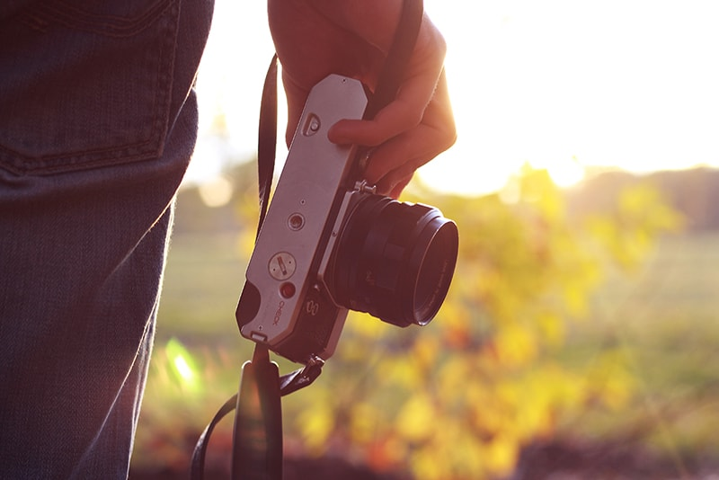 Photography business - person outdoors holding camera down by their side