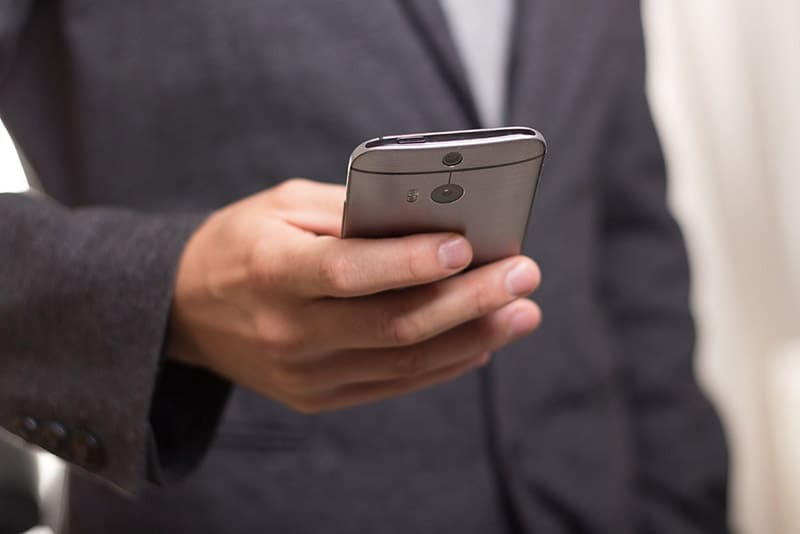 How CYOD tackles the cybersecurity concerns of BYOD - person holding mobile phone