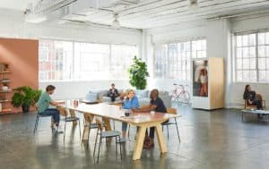Build a successful startup - people sitting on a chair at a tavle inside large open plan room