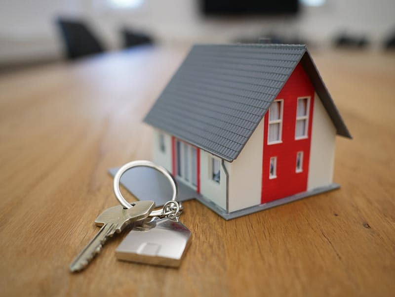 Property Management white and red wooden house miniature on brown table next to a property key