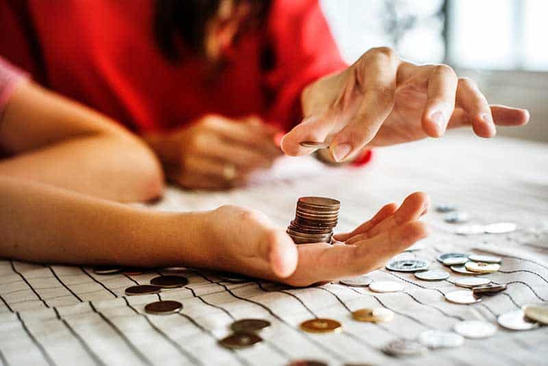 Importance of teaching financial education - mother and child counting coins