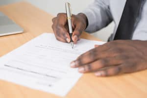 The Risks You Should be Aware of When Signing a Personal Guarantee Form - person signing document with silver and black fountain pen