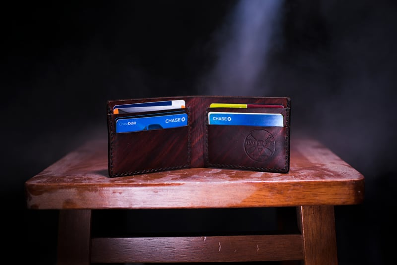 brown leather bifold wallet on table containing credit cards