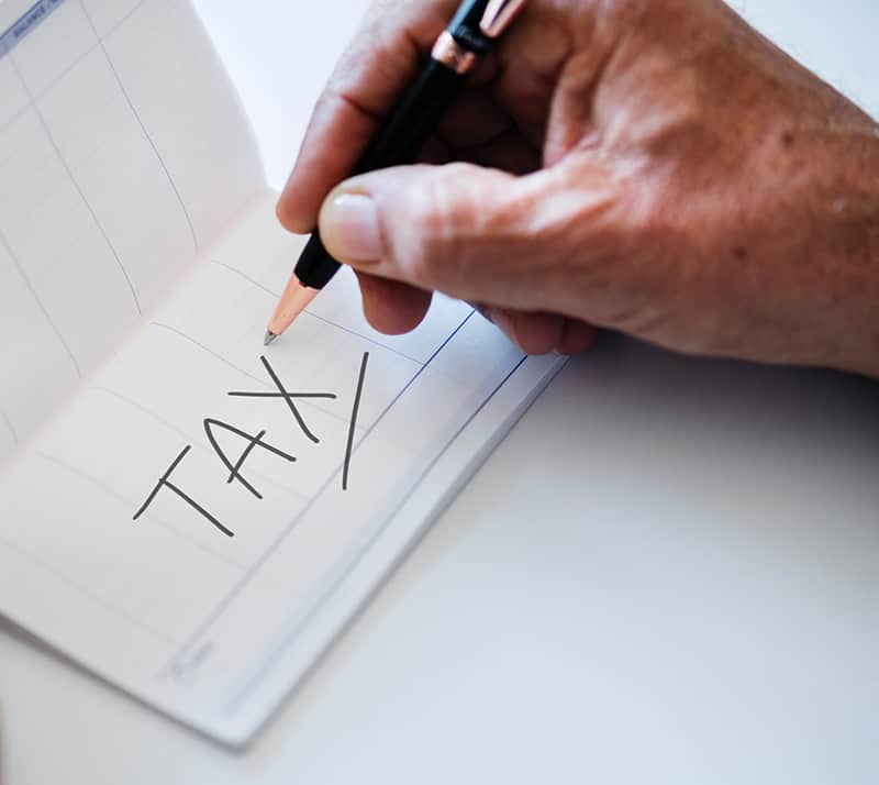 Person holding a black pen – tax written in notebook