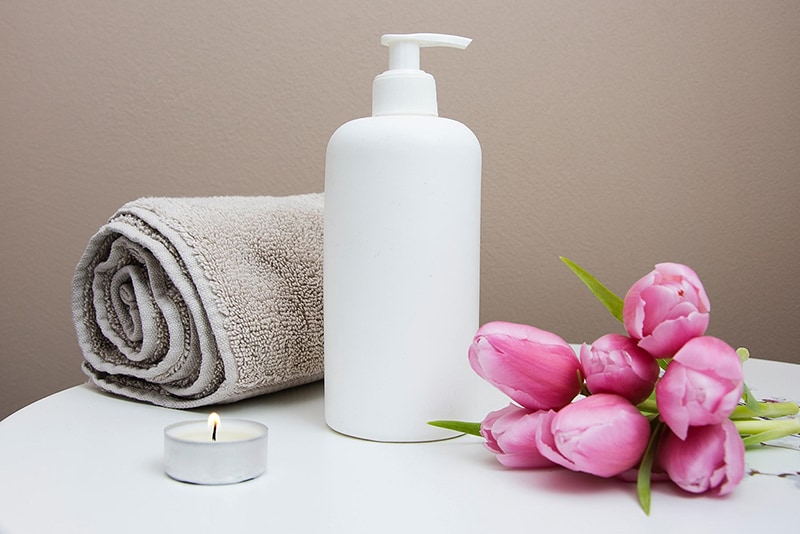 Towel, lotion, candle and flowers for Massage therapist