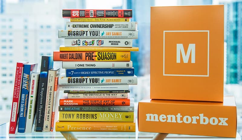 Mentorbox product packaging and pile of business books