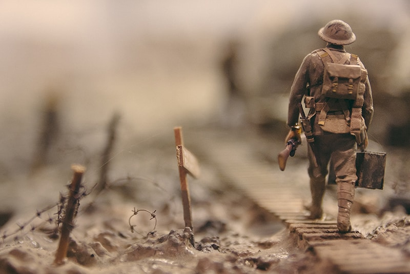 soldier walking on wooden pathway surrounded with barbwire selective focus photography - warfare