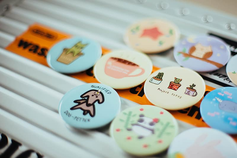 assorted-color custom badges on top of white surface