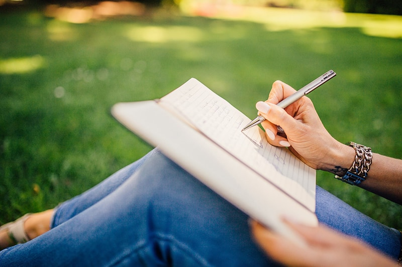 person sitting on grass writing in a book
