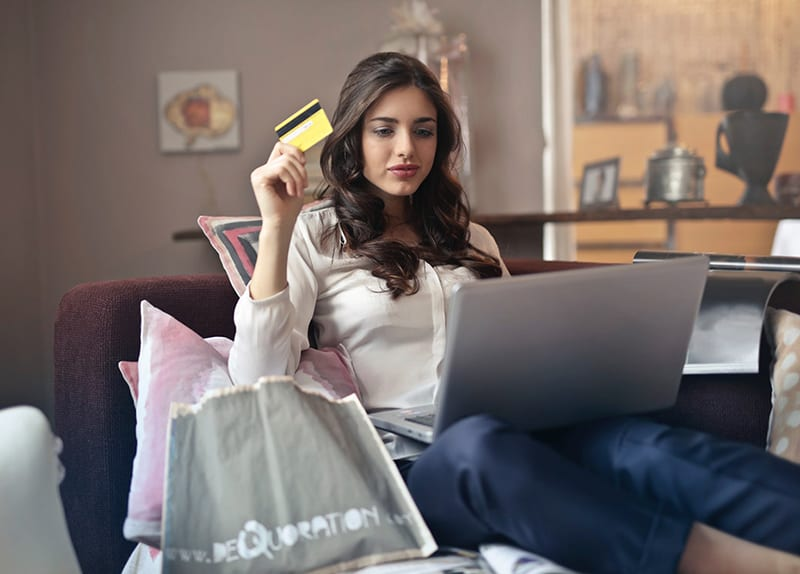 womanholding credit card and computer making purchase from ecommerce site