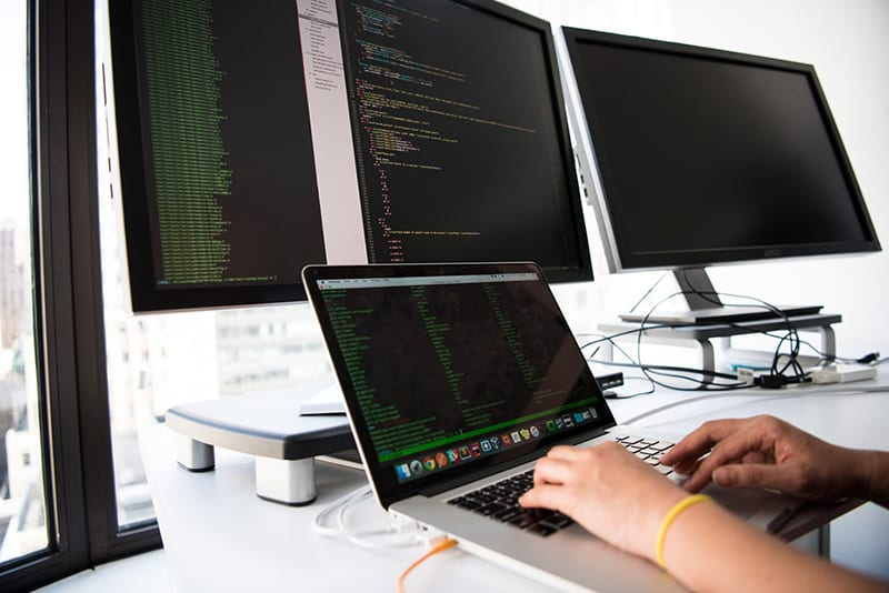 IT personnel typing on laptop connected to dual monitors.