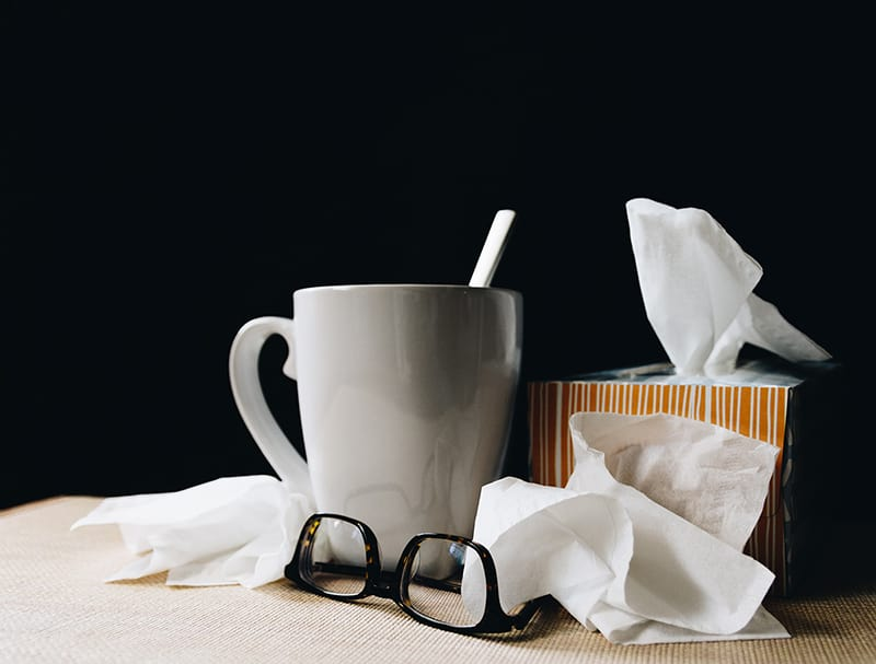 ceraminc mug next to tissues and glassess - health and wellbeing