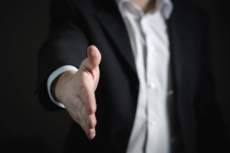 Is Buying into a Franchise a Good Idea - man holding out his hand