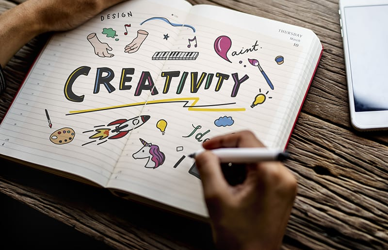 "Person doodling pictures and the word ""creativity"" in a notebook."