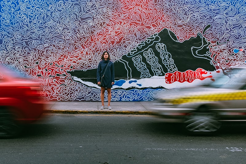 time lapse photography of woman standing on pavement in front of trainer artwork on wall