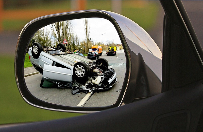 overturned vehicle due to road accident seen in car wing mirror