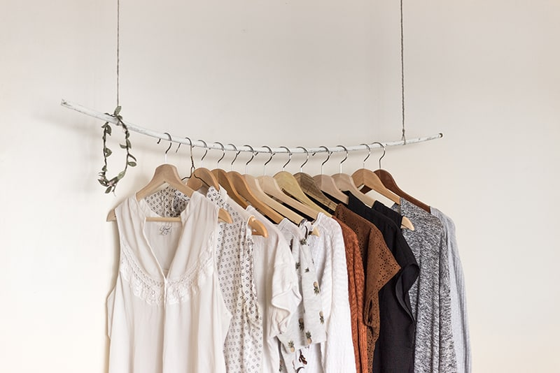Fast fashion - clothes rail with garments hanging from it.