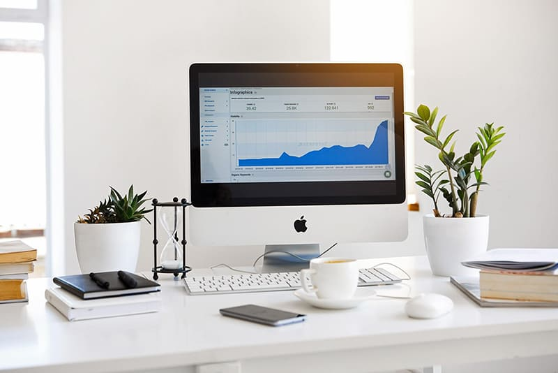 White desk withbooks, plants and apple device monitoring SEO traffic