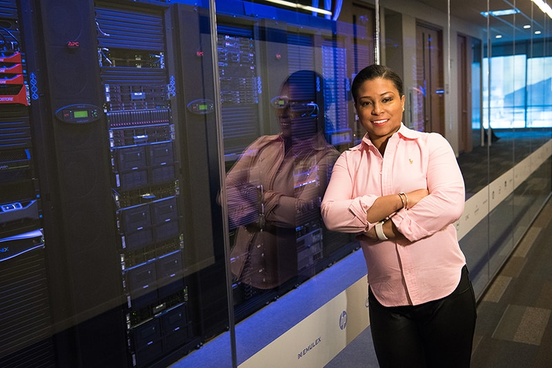 Woman standing outside data server room – leaning against glass wall.