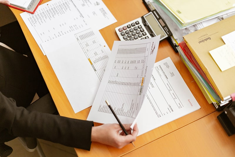 Accountant holding piece of paper, calulator on desk
