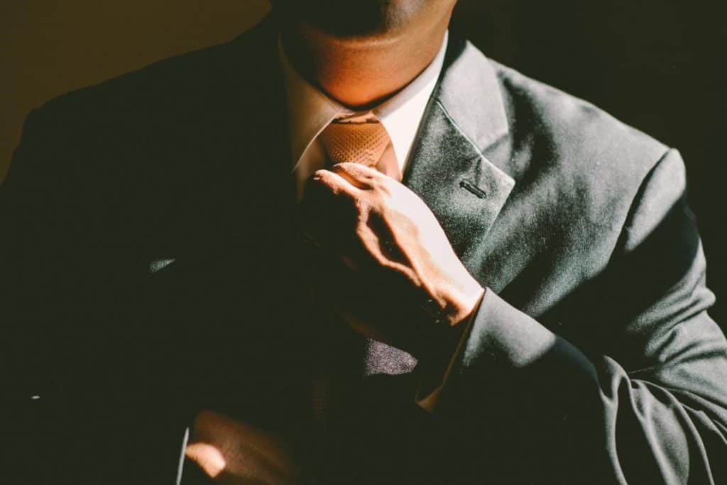 Businessman in suit fixing his neck tie