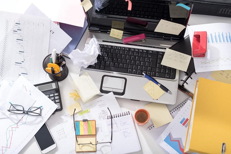 clutter untidy desk - chaos - office organization required.