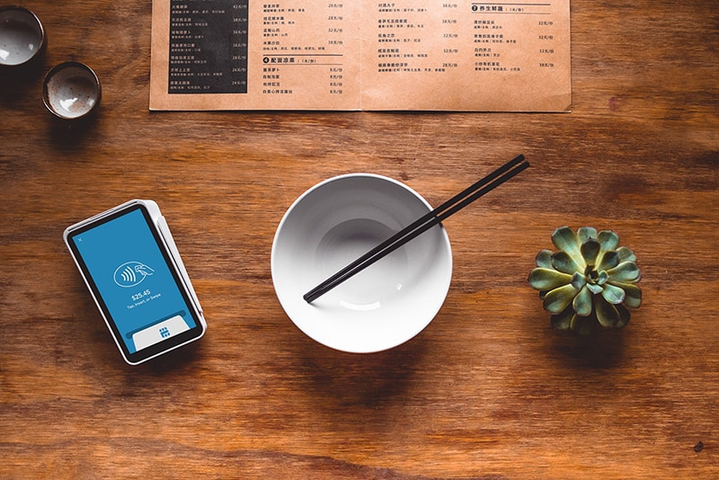 white ceramic bowl with chopsticks, nect to a plant and card reader