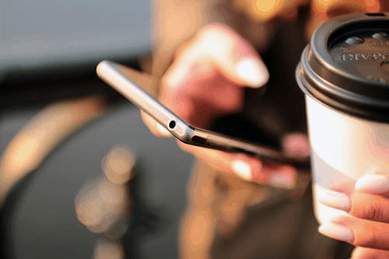 Person using mobile application and holding disposable coffee cup