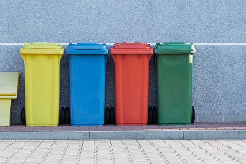 four assorted-color solid waste trash bins beside gray wall