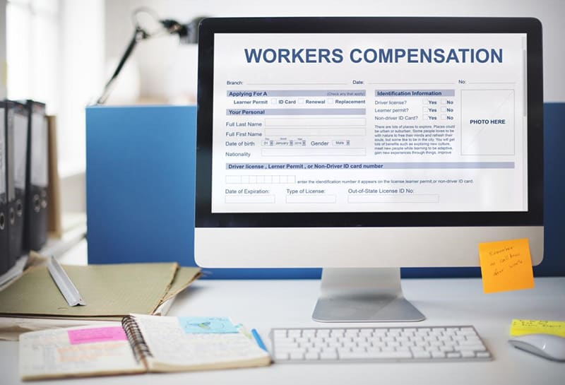 Computer monitor on desk with workers comp information on it