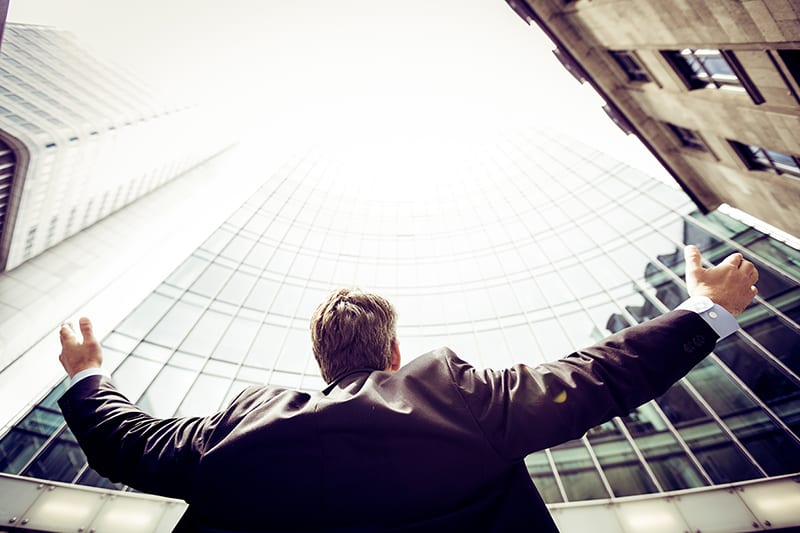 low angle photography of man outside in the middle buildings