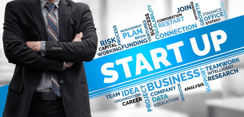 Entrepreneur standing next to business startup word cloud