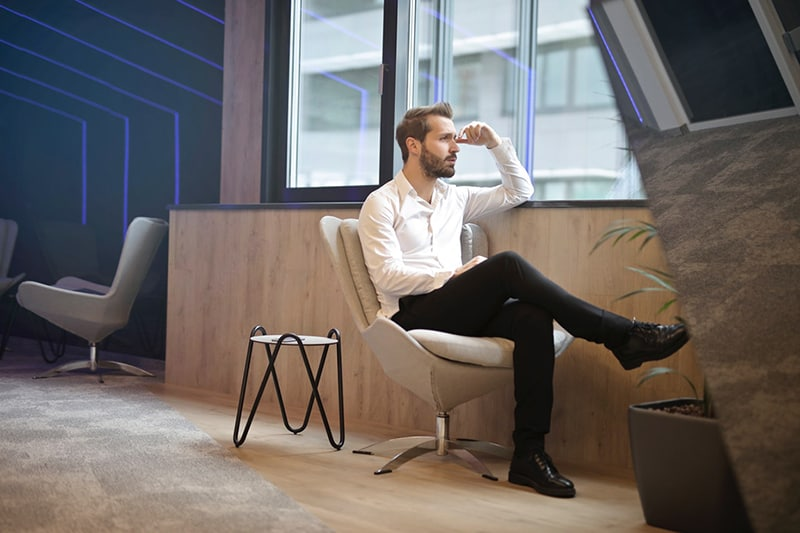 Man sitting in chair near window and looking out following unfair dismissal