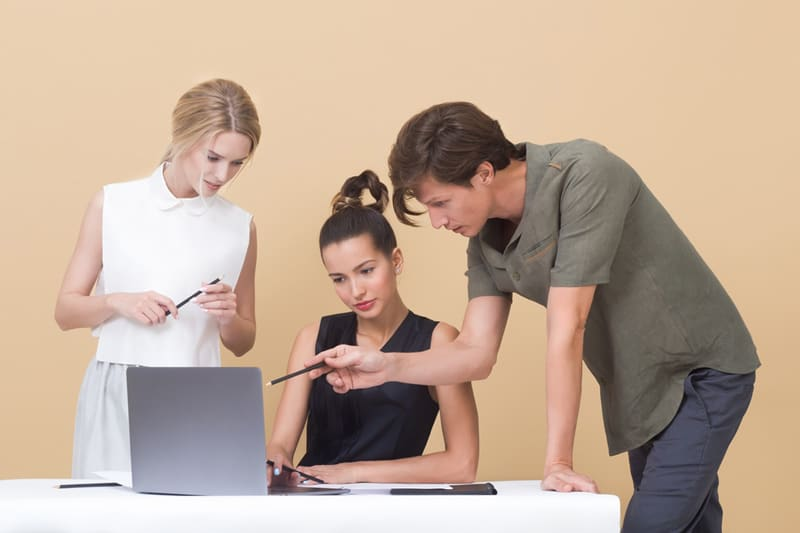 Two women and a man looking and pointing at a laptop