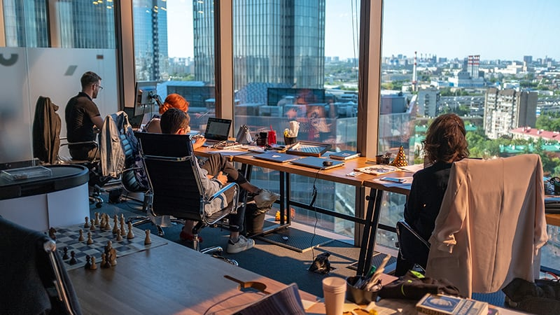 People sitting at a desk in an office in high rise building