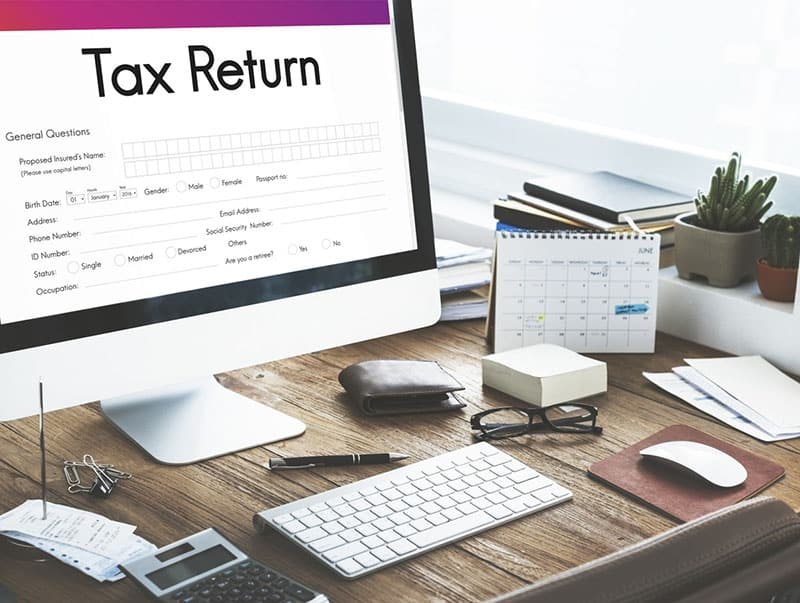 Tax return form on monitor screen on a desk with keyboard mouse calulator and other items
