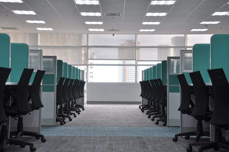 empty black rolling chairs at office workstation cubicles