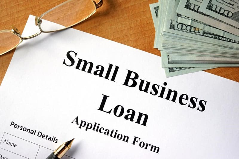 Small business loan application form on table next to dollar bills