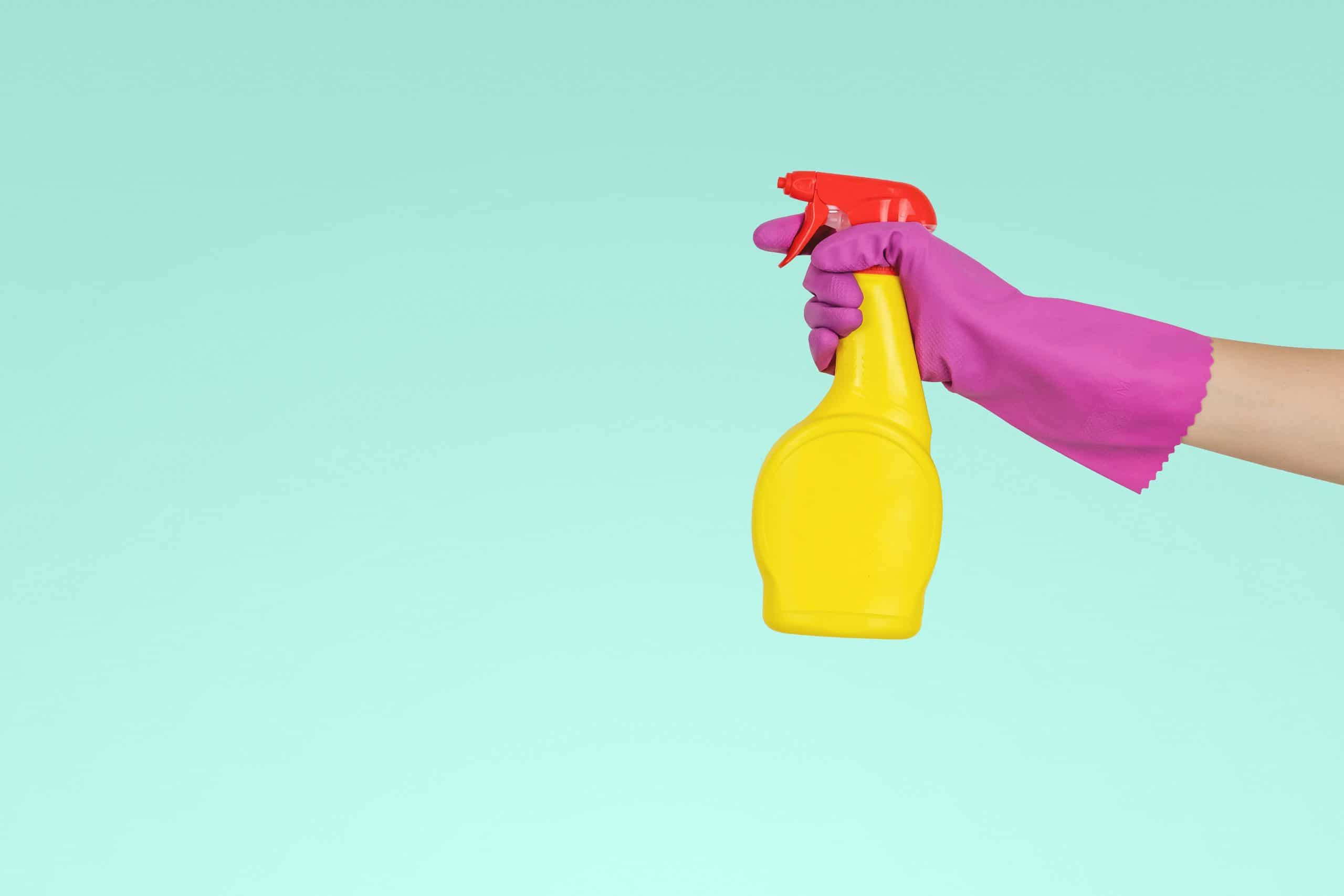 person holding yellow plastic spray bottle of cleaning products