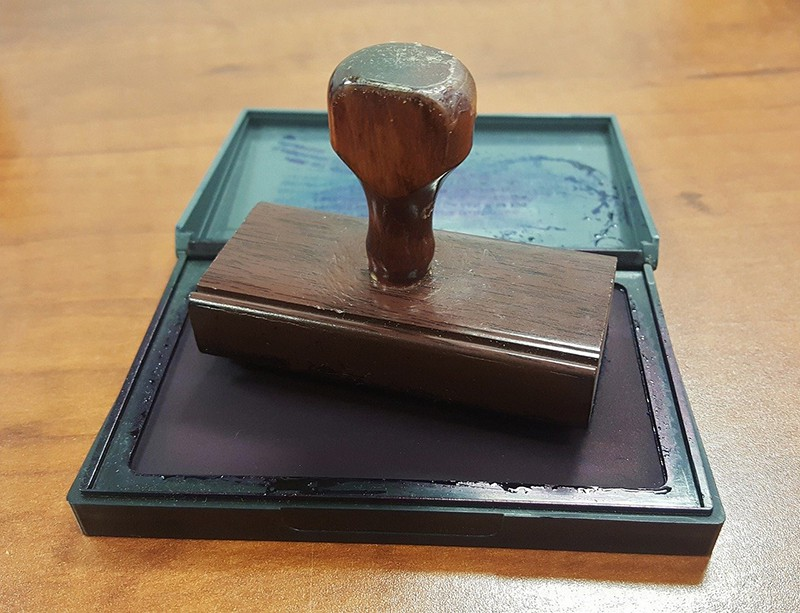 Rubber stamp and ink pad on table