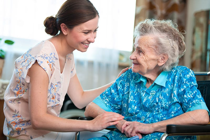 A healhcare woman and an old woman in a wheelchair