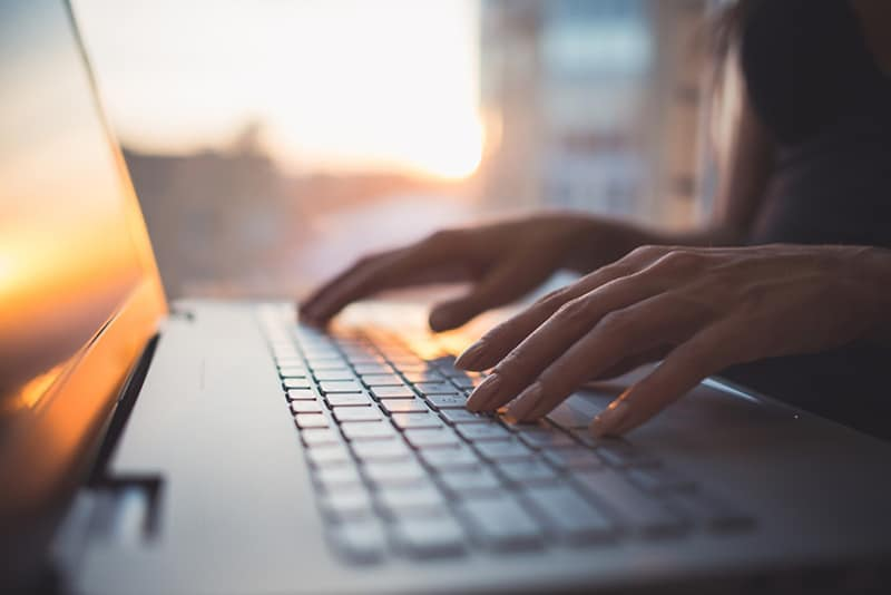 Woman typing on keyboard with sun reflecting off laptop screen