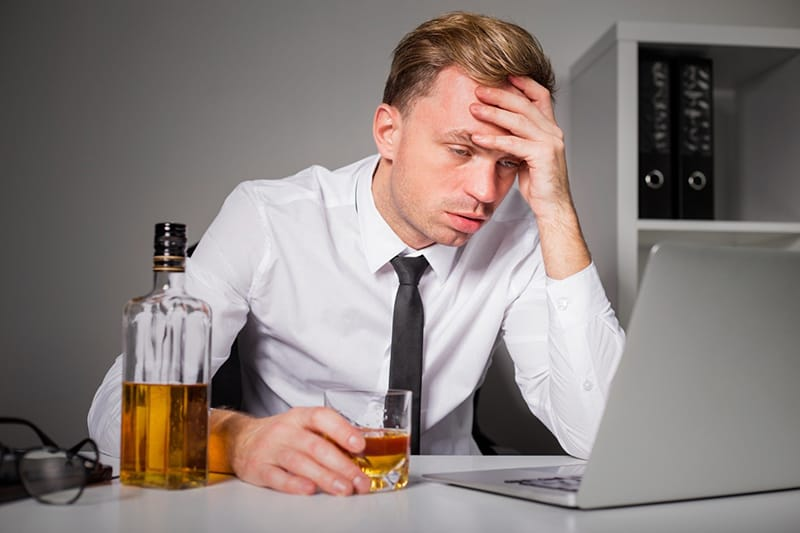 Man sitting at desk - perfomance affected due to drinking alcohol