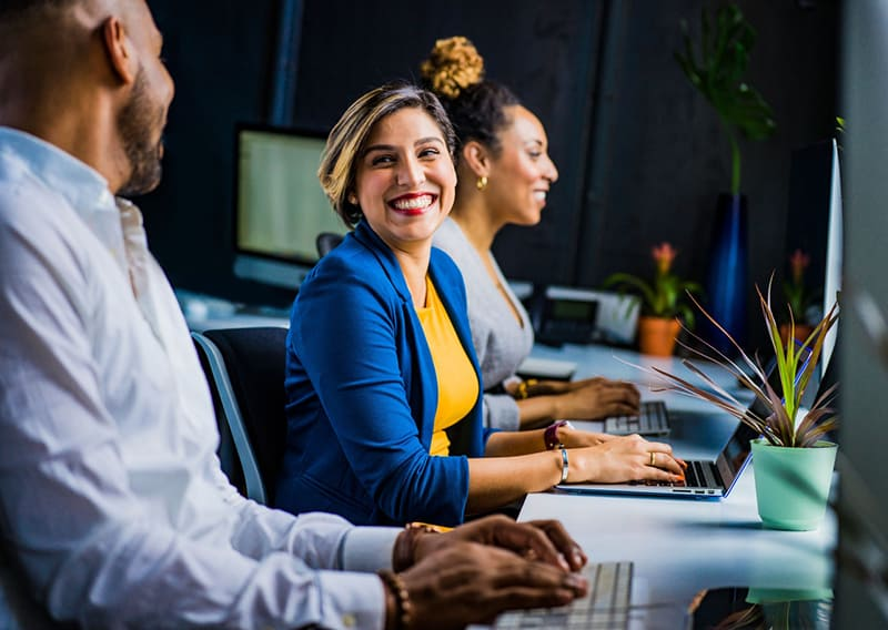 Woman in blue jacket alongside colleagues in a business startup