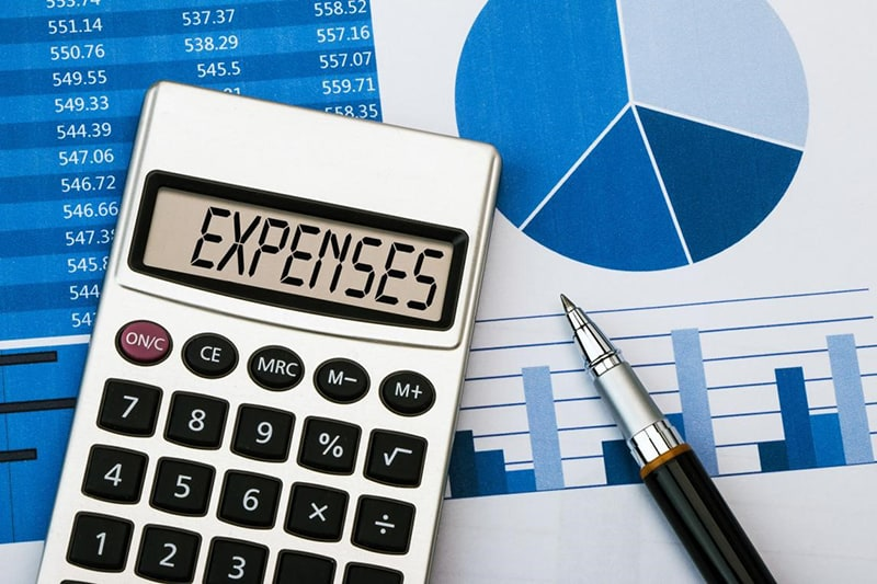 Keeping Track of Business Expenses - calculator, pen and expenses sheet