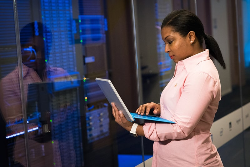 Woman holding a laptop outside computer server room